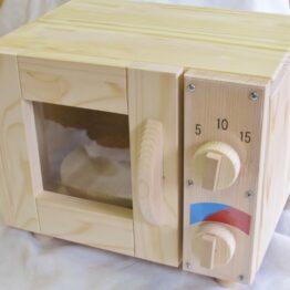 手作り木製ままごとレンジです。中に木製のターンテーブルが在り手動でくるくる回せます。右側にはダイヤルが二つあり、それも手動でくるくる回せます。
